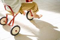 三輪車に乗る少年の足元