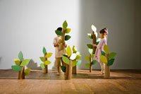 ダンボール製の木を運ぶ少年少女2人