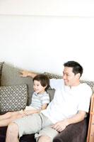 ソファでくつろぐ父と息子