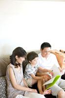 ソファで本を読む家族3人