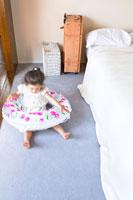 ベッドの横で浮き輪をつける少女