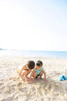 砂浜で遊ぶ少年と少女