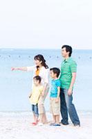 海辺に立ち微笑む家族4人