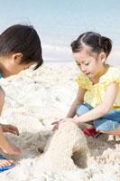 砂浜で砂遊びをする少年と少女