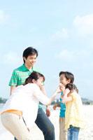 砂浜で貝殻を見る家族4人