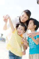 砂浜で貝殻を見る家族3人