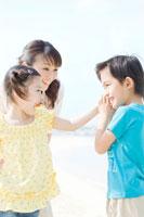 貝殻で遊ぶ家族3人