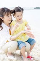 貝殻を見る母と少女