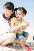 砂浜で遊ぶ母と少女