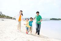 砂浜を走る家族4人