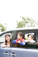 車から顔を出す家族3人