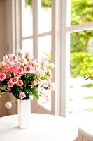 窓辺に置かれた花瓶のピンクのバラ