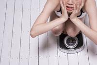 体重計に乗り困惑する女性