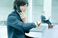 電話中に時間を確認するビジネスマン