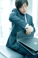 携帯電話で話しながら鞄を開けるビジネスマン
