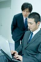 パソコンを操作する男性を覗くビジネスマン