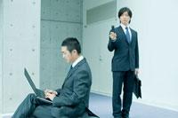 パソコンを操作する男性を盗撮するビジネスマン
