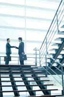 オフィスビルの階段で握手をするビジネスマン