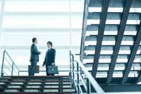 オフィスビルの階段で立ち話をするビジネスマン