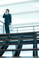 オフィスビルで携帯電話で話すビジネスマン 24031000016  写真素材・ストックフォト・画像・イラスト素材 アマナイメージズ