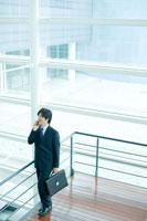 オフィスビルで携帯電話で話すビジネスマン
