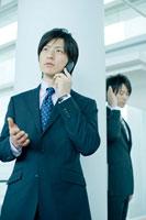 携帯電話の会話を盗み聞きするビジネスマン