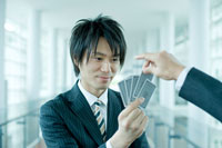 トランプカードを引かせるビジネスマン