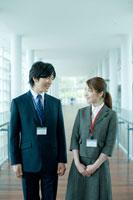 廊下で見つめ合うビジネスマンとビジネスウーマン