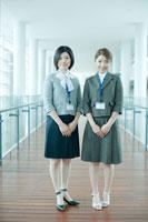 オフィスの廊下に立つ女性社員 24031000052| 写真素材・ストックフォト・画像・イラスト素材|アマナイメージズ