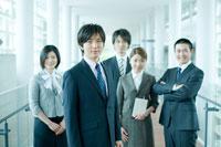 オフィスの廊下に立つ男女社員 24031000054| 写真素材・ストックフォト・画像・イラスト素材|アマナイメージズ