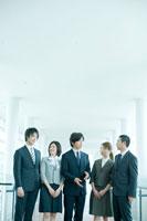 オフィスの廊下に立つ男女社員 24031000059| 写真素材・ストックフォト・画像・イラスト素材|アマナイメージズ