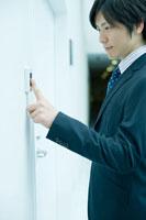 指紋認証システムに指をかざすビジネスマン