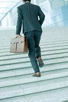 階段をかけあがるビジネスマン