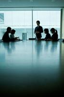 会議室で話し合う男女社員