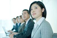会議室で一列に並んで座る男女社員
