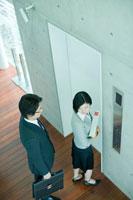 エレベーター前で女性の背後に立つ男性社員