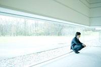 窓際に座り込むビジネスマン