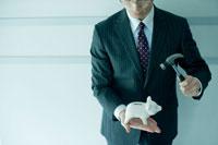 豚の貯金箱と金づちを持つビジネスマン