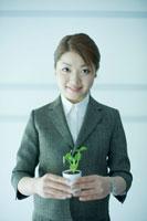 観葉植物を持つビジネスウーマン