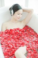 フラワーバスで音楽を聴く女性 24031000160A| 写真素材・ストックフォト・画像・イラスト素材|アマナイメージズ