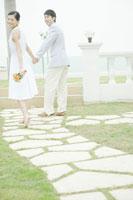 ブーケを持つ女性と手を繋いで歩く男性