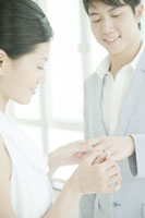 男性の薬指に指輪をはめる女性
