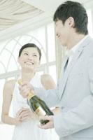 シャンパンボトルを持つ男性と側で笑う女性