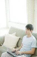 ソファーの上でパソコンをする男性 24031000222| 写真素材・ストックフォト・画像・イラスト素材|アマナイメージズ
