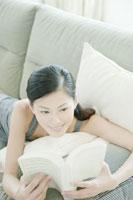 ソファーの上で読書する女性