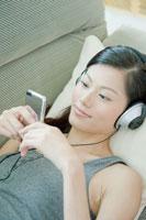 ソファーの上で音楽を聴く女性