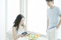 サラダを食べる女性と側で微笑む男性