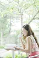 カフェでコーヒーを飲みながら読書する女性 24031000263| 写真素材・ストックフォト・画像・イラスト素材|アマナイメージズ