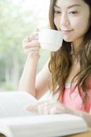 カフェでコーヒーを飲みながら読書する女性