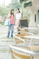 カフェの前でメニューを確認する女性たち